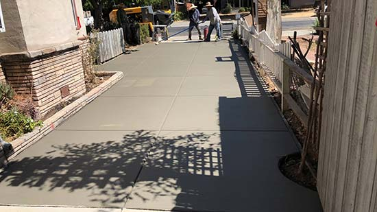Two concrete contractors finishing a concrete driveway in Fremont California