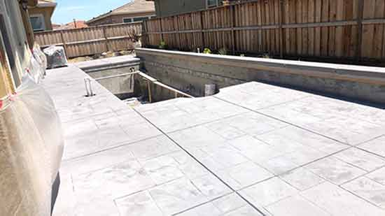 Concrete pool deck in backyard of Fremont California house